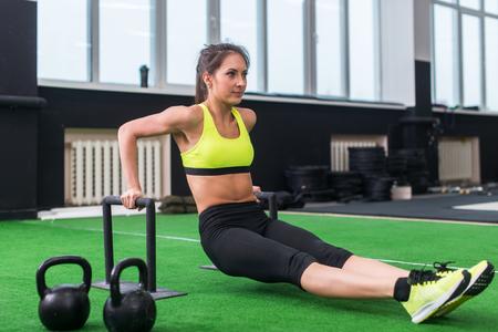 cuerpo femenino: lateral de una mujer deportiva haciendo ejercicios l-se sienta con las barras en el gimnasio.