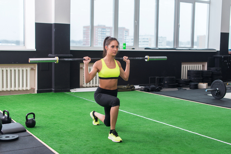 lunges: athletic woman doing lunges with barbell, working out legs and glute muscles. Stock Photo