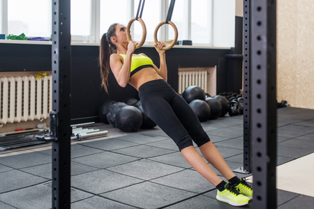 pullups: fit woman doing pull-ups with gymnastic rings in gym, young female working out biceps, triceps, abs.