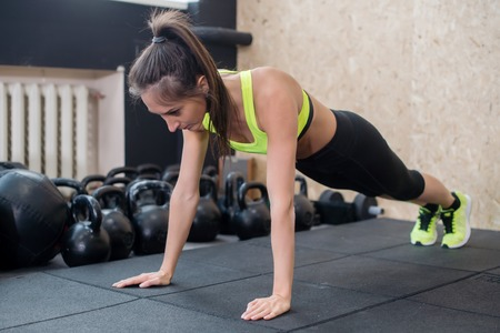 arm muscles: fit woman doing push-ups on the floor, sporty female working out abs, arm muscles.