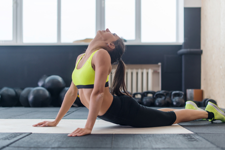 arching: young female doing back stretching exercise, fit woman warming-up in gym.