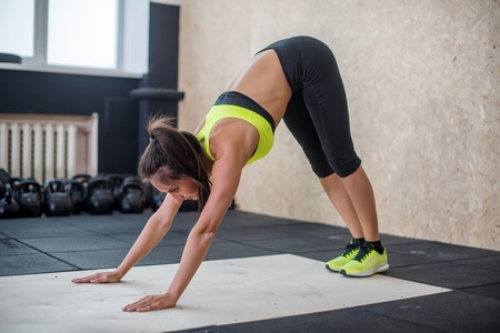 facing: fit woman performing downward dog pose, doing yoga in gym.