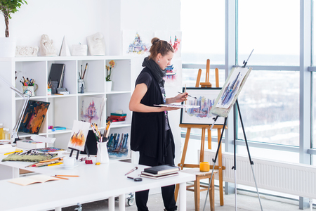 Female painter drawing in art studio using easel. Portrait of a young woman painting with aquarelle paints on white canvas, side view portrait.