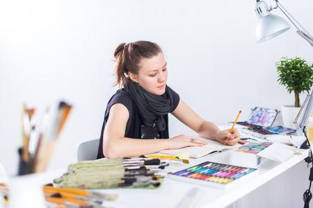 Hembra joven artista boceto de dibujo usando cuaderno de dibujo con el lápiz en su lugar de trabajo en el estudio. Vista lateral retrato de pintor inspirado