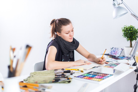 Young female artist drawing sketch using sketchbook with pencil at her workplace in studio. Side view portrait of inspired painter Standard-Bild