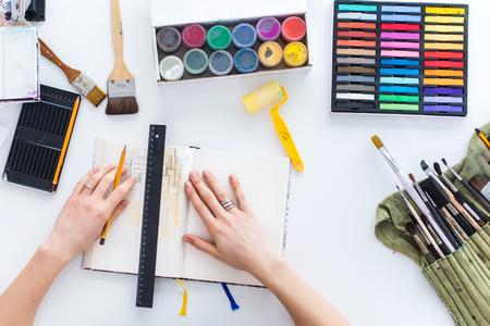 Vista superior cuadro del pintor bosquejo de drenaje en el cuaderno de dibujo utilizando lápices, lápices de colores y pinturas de la gouache. Pintura del artista en el taller