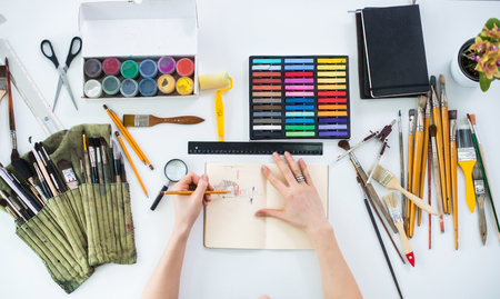 Female artist drawing graphic sketch at sketchbook with pencil in art gallery, her workplace. Top view photo of artistic tools lying on work-table: gouache, crayons palette and paintbrush collection