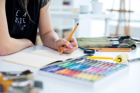 Punto di vista di angolo del primo piano di un tiraggio del disegno del pittore femminile allo sketchbook facendo uso della matita. Artista che abbozza nello studio di arte con i pastelli impostati