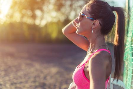 muscle training: Attraktive fit Frau in Sportkleidung Training im Freien, Sportlerin mit perfekten Körper nach Training stillsteht, Mode-Sport-Modell gesunden Lebensstil. Lizenzfreie Bilder