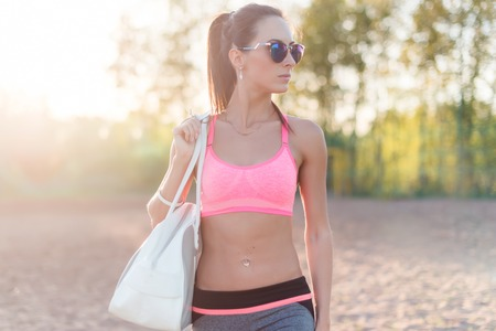 abdominal fitness: Attractive fit woman in sportswear training outdoors, female athlete with perfect body resting after workout, fashion sport model healthy lifestyle. Foto de archivo