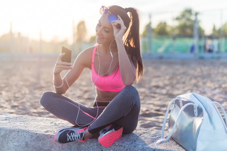 work out: Beautiful fitness athlete woman wearing sunglasses resting listening music after work out exercising on summer evening in beach at sunset with smartphone outdoor portrait