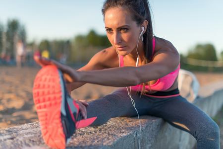 hamstring: Fitness model athlete girl warm up stretching her hamstrings, leg and back. Young woman exercising with headphones listening music outdoors on beach or sports ground at evening summer.