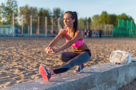 lithe: Fitness model athlete girl warm up stretching her hamstrings, leg and back. Young woman exercising with headphones listening music outdoors on beach or sports ground at evening summer.