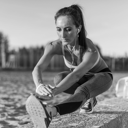 hamstrings: Fitness model athlete girl warm up stretching her hamstrings, leg and back. Young woman exercising with headphones listening music outdoors on beach or sports ground at evening summer.