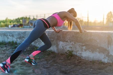 Fitness vrouw doet push ups Outdoor workout zomeravond. Concept sport gezonde levensstijl