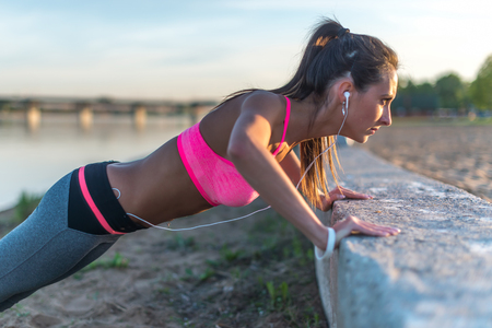 doing: Fitness woman doing push ups Outdoor training workout summer evening. Concept sport healthy lifestyle