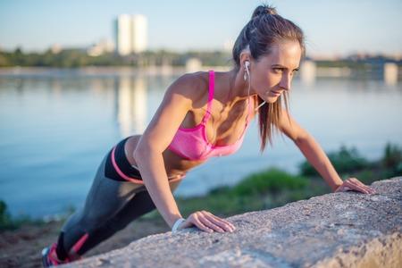 Mujer de la aptitud que hace pectorales al aire libre sesión de entrenamiento de la vista lateral noche de verano deporte Concepto de estilo de vida saludable