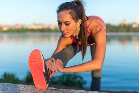 legging: Athletic woman stretching her hamstring, legs exercise training fitness before workout outside on a beach at summer evening with headphones listening music. Stock Photo
