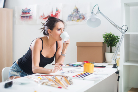 Young artist drawing watercolor picture sideview, holding cup of coffee. photo