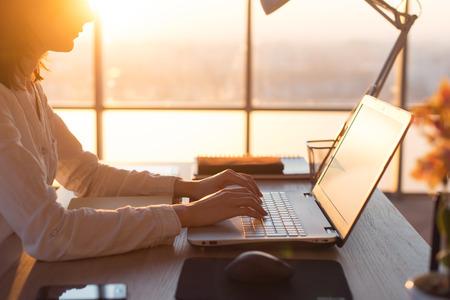 ノート パソコンとインターネット、オンラインでの作業を使用して女性のテレワーカー テキスト メッセージ。フリーランサー入力自宅、オフィス