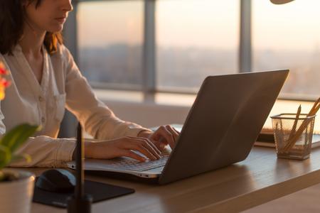 Vista lateral foto de un programador mujer usando la computadora portátil, trabajando, escribir, navegar por internet en el lugar de trabajo