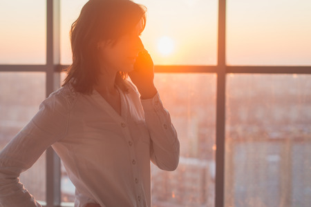 llamando: mujer joven ocupada con llamar, hablar por teléfono celular vista lateral retrato. Foto de primer plano de una mujer de negocios la celebración de dispositivo móvil en su lugar de trabajo