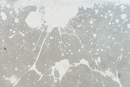 splotchy: White splash on gray background concrete wall, messy, splotchy, surface. Decorative wet paint drops, abstract art Stock Photo