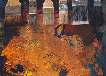 canvas art: Paintbrush set lying on an old palette with oil paint brushstrokes top view photo