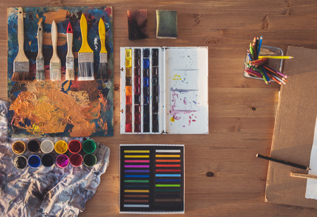 work table: Painting tools: gouache, watercolor, crayons set, palette and paintbrush collection arranged, prepared for drawing in art studio