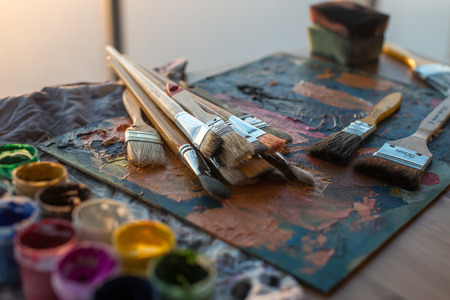 Drawing classes tools in art studio. Angle view photo of paintbrushes lying on palettewith oil paints brushstrokes mixture