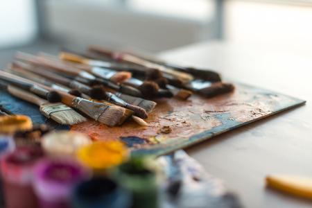 alumnos en clase: Primer plano vista lateral imagen de una colección de la brocha de madera situada en la paleta de edad y aguada situado en la sala de trabajo con luz natural