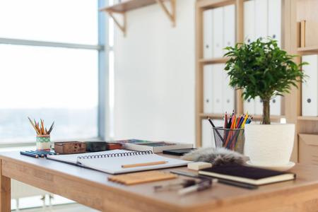 pastel colors: Vista lateral de un espacio de trabajo de pintor. escritorio de madera con herramientas artísticas preparadas por el dibujo en colores pastel