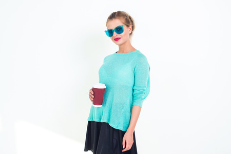 messy hairstyle: Woman wearing mint blue sunglasses and top with messy hairstyle, smiling. Portrait of fit blond glamorous female model posing, holding red coffee cup on white background, not isolated