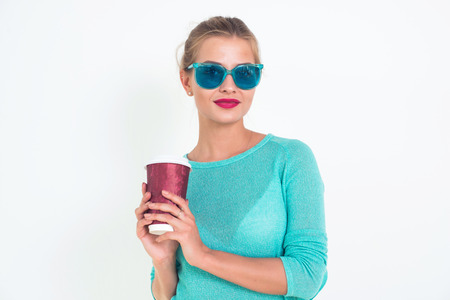 messy hairstyle: Beautiful female holding cup of hot coffee to go, wearing fashionable blue sunglasses, blouse and bright make-up with messy hairstyle, close-up portrait, not isolated