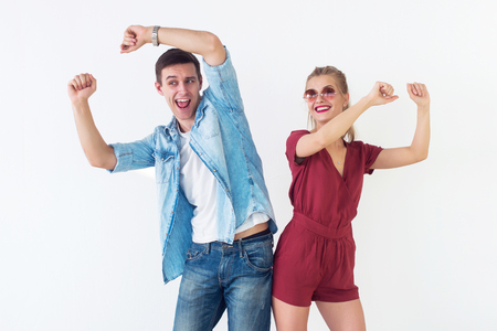 Active young couple of friends having good time, raising hands up, dancing, laughing together on white background Archivio Fotografico