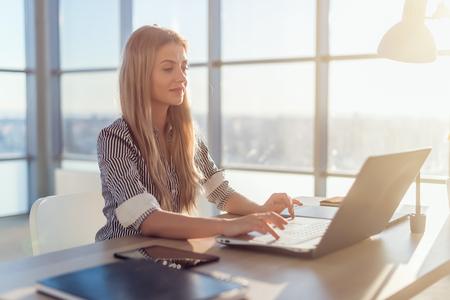 belos textos jovens copywriter fêmea de digitação e blogs em escritório claro espaçosos, seu local de trabalho, usando teclado do PC. Mulher ocupada trabalhando Imagens - 55663989