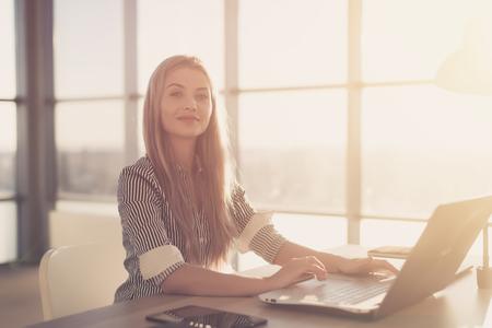 usando computadora: Mujer en los blogs amplia oficina que usa el ordenador en su lugar de trabajo. Empleado de sexo femenino que se sienta, sonriendo, mirando a la cámara