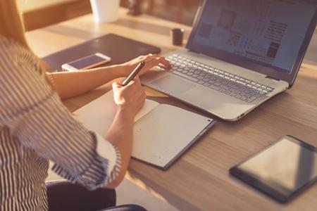 空白のメモ帳にスケッチするラップトップを使用して女性デザイナー。木製の机の上のノートで手書きの女性