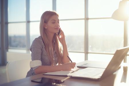 preguntando: Vista lateral retrato de la joven empresaria que tiene llamada de negocios en la oficina, su lugar de trabajo, escribir alguna información. Mujer hablando por teléfono móvil, haciendo preguntas, mirando la pantalla del PC Foto de archivo
