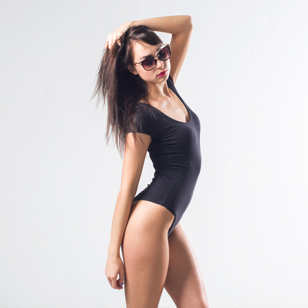 Attractive female standing sideways, holding her hair, keeping hand along body, wearing black bodysuit. Portrait of brown-haired woman posing in sunglasses, not isolated