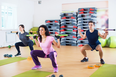 squats: People exercising in gym doing squats working out with barbells in fitness club