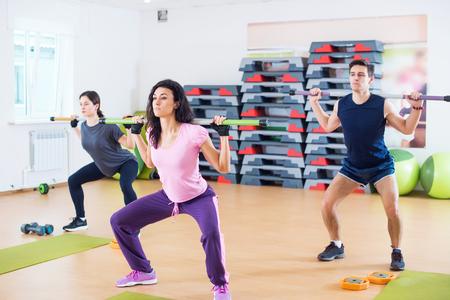 cuclillas: Grupo de personas excercising con las barras en la gimnasia que hace en cuclillas con una barra en el club de fitness.