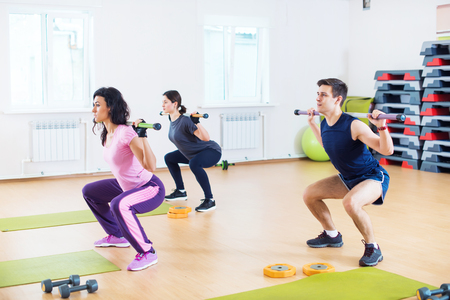 People doing squats with barbells on shoulders exercising at fitness club Stock Photo