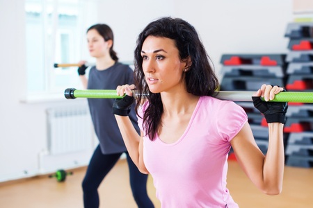 squatting: Group of people excercising with bars in gym doing squatting with a barbell at fitness club. Stock Photo
