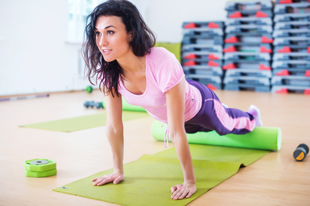 roller: Fit woman stretching on floor using foam roller doing plank exercise, push ups. Stock Photo
