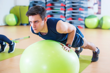 pilates man: Fit man exercising with fit ball workout out arms Exercise training triceps and biceps doing push ups