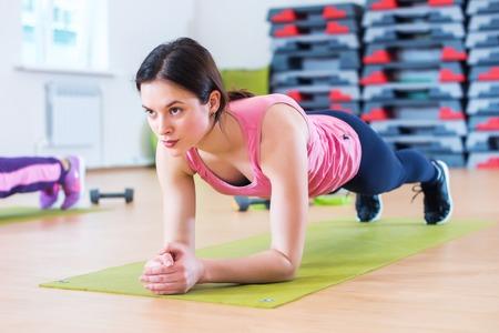 nucleo: Ajuste a la mujer juguetona que hace entrenamiento de la base tablón de ejercicio para la espalda y los músculos de prensa concepto power gym sportsman entrenamiento físico fuerza