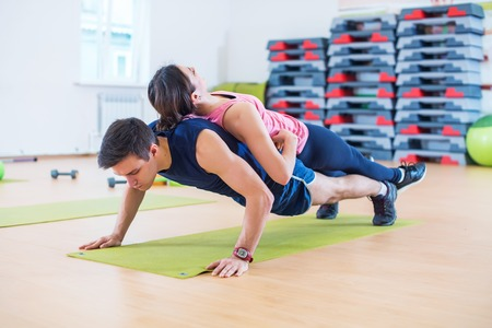 musculine: Fit man doing push-ups with woman on back in gym using own weight. Sport training arms, teamwork
