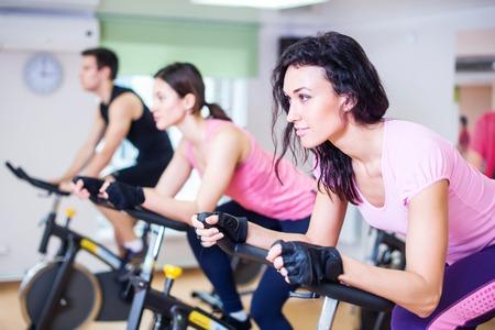 Training di gruppo di persone in bicicletta in palestra, esercitando le gambe facendo allenamento cardio ciclismo biciclette. Archivio Fotografico