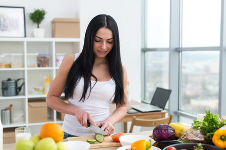 vegetable cook: Female cook slicing green cucumber, cooking fresh vegetable salad on cutting board at her kitchen worktop